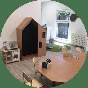 pomieszczenie zdrewnianym domkiem stolikiem ikrzesełkami